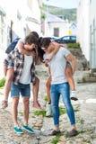 Hommes de hanche donnant sur le dos à leurs amies et à l'aide du smartphone Image libre de droits