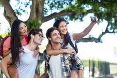 Hommes de hanche donnant sur le dos à leurs amies et prenant le selfie Image stock
