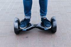 Hommes de jambe dans les espadrilles et des jeans se tenant sur la plate-forme bleue Commencez à employer le scooter, le hoverboa Image stock