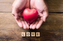 Hommes de mains donnant le coeur et le mot rouges pour l'amour Image stock