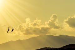 Hommes de silhouette accrochant la corde de câble Photographie stock