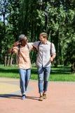Hommes de sourire étreignant tout en marchant en parc ensemble Photographie stock