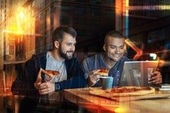 Hommes de sourire regardant l'écran tout en mangeant de la pizza ensemble Image stock