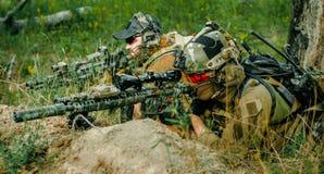 Hommes de tireur isolé d'Airsoft avec des armes à feu étendues sur la colline Tireur isolé et viseur sur l'opération photo stock