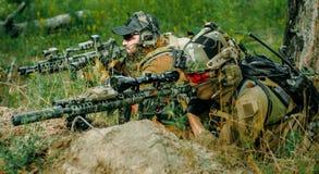 Hommes de tireur isolé d'Airsoft avec des armes à feu étendues sur la colline Tireur isolé et viseur sur l'opération image libre de droits