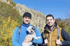 Hommes de touristes dans la montagne d'automne avec leur chien Photo stock