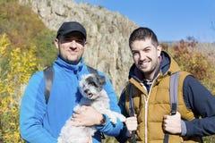 Hommes de touristes dans la montagne d'automne avec leur chien Photographie stock