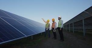 Hommes discutant les panneaux solaires sur le champ de plantation image stock