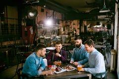 Hommes en bière de bar et nourriture potables de consommation Photo stock