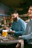 Hommes en bière de bar et nourriture potables de consommation Images stock