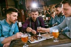 Hommes en bière de bar et nourriture potables de consommation Photos stock
