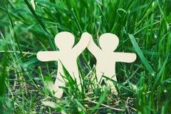 Hommes en bois tenant des mains dans l'herbe Image stock