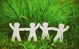 Hommes en bois tenant des mains dans l'herbe Photos libres de droits