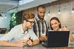 Hommes et femme insouciants à l'aide de l'ordinateur portable dans le cafétéria Photo stock