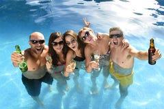 Hommes et femmes attirants heureux dans le bikini ayant le bain à la bière potable de piscine de station de vacances d'hôtel Photographie stock