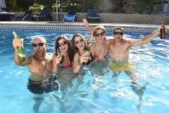 Hommes et femmes attirants heureux dans le bikini ayant le bain à la bière potable de piscine de station de vacances d'hôtel Photo stock