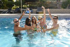 Hommes et femmes attirants heureux dans le bikini ayant le bain à la bière potable de piscine de station de vacances d'hôtel Image libre de droits