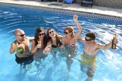 Hommes et femmes attirants heureux dans le bikini ayant le bain à la bière potable de piscine de station de vacances d'hôtel Photos stock