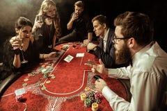 Hommes et femmes avec des boissons jouant le tisonnier dans le casino Photographie stock libre de droits
