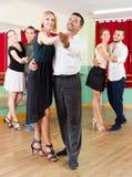 Hommes et femmes ayant la classe de danse dans le studio Photo libre de droits