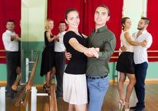 Hommes et femmes ayant la classe de danse dans le studio Image stock
