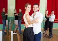 Hommes et femmes ayant la classe de danse dans le studio Images libres de droits