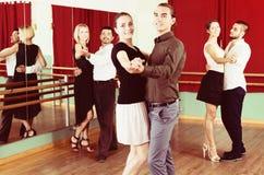 Hommes et femmes ayant la classe de danse dans le studio Photo stock