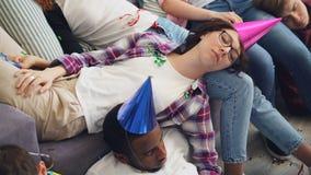 Hommes et femmes dans le chapeau de partie dormant sur le divan et le plancher après célébration à la maison banque de vidéos