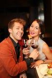 Homme et femme avec un verre de vin observant l'appareil-photo Image stock