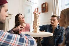 Hommes et femmes jouant le jeu de jenga à la maison Image libre de droits