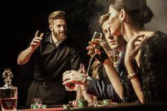 Hommes et femmes jouant le tisonnier dans le casino Photographie stock libre de droits