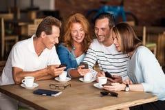 Hommes et femmes positifs à l'aide des téléphones intelligents Images libres de droits