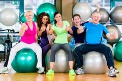 Hommes et femmes s'asseyant sur des boules de forme physique dans le gymnase Photographie stock libre de droits