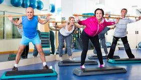 Hommes et femmes s'exerçant dans un gymnase Photos stock