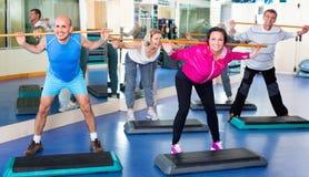Hommes et femmes s'exerçant dans un gymnase Photo stock
