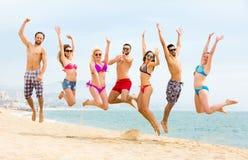 Hommes et femmes sautant sur la plage Photographie stock libre de droits