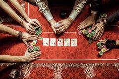 Hommes et femmes tenant des jetons de poker dans le casino Photographie stock