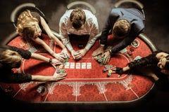 Hommes et femmes tenant des jetons de poker dans le casino Images libres de droits