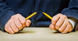 Hommes fâchés cassant un crayon Photographie stock