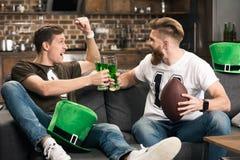 Hommes faisant tinter des verres de bière au jour de patricks de St Images stock