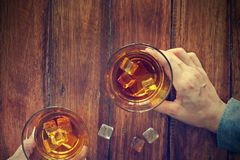 Hommes faisant tinter des verres de whiskey dans la nuit de partie Images stock