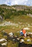 Hommes filtrant l'eau du flot 2 de montagne photographie stock