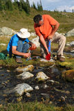 Hommes filtrant l'eau du flot 4 de montagne image stock