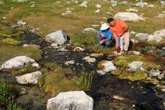 Hommes filtrant l'eau du flot de montagne images stock