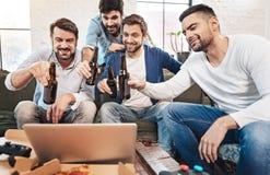 Hommes gais heureux buvant de la bière avec leurs amis en ligne Images stock