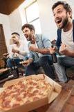 Hommes gais heureux observant une partie de football Images stock