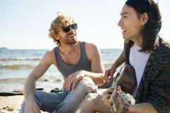 Hommes gais jouant la guitare sur la plage Image stock