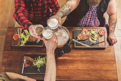 Hommes gais s'asseyant à la table en bois dans la barre Photographie stock