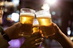 Hommes grillant avec de la bière tout en se reposant dans le bar ensemble Images libres de droits