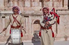 Hommes habillés dans le costume national On joue le tambour et les autres jeux les cornemuses dans Roman Theater du nord antique image libre de droits